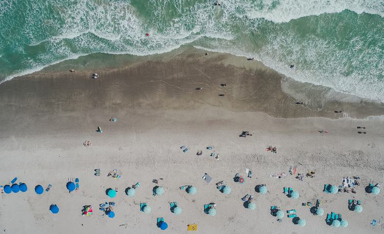 Aerial View of Sandy Beach with Tourists