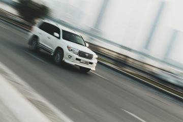 White Car Moving against Blurred Background