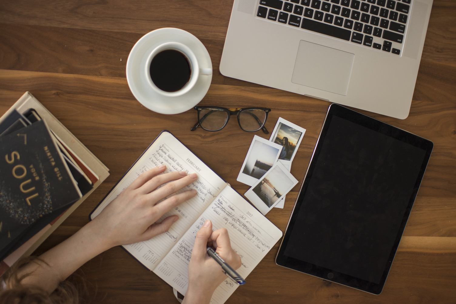 Top View of Hand Writing on a Notebook, with Laptop, Tablet and Hot Coffee