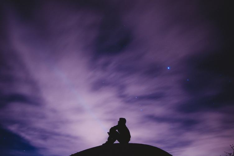 Silhouette of Sitting Man on a Hill Watching the Night Sky