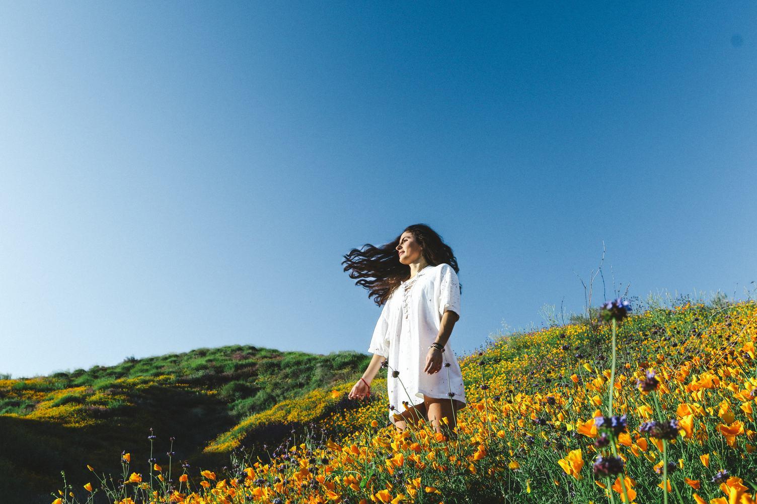 Woman at Blooming Orange Poppy Field