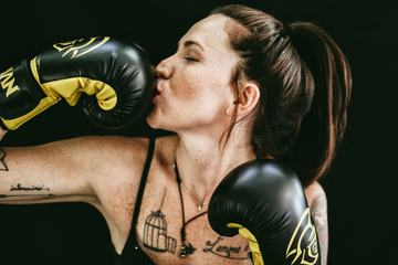 Woman Kissing her Boxing Gloves over Black Background