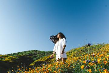 Woman at Blooming Orange Poppy Field