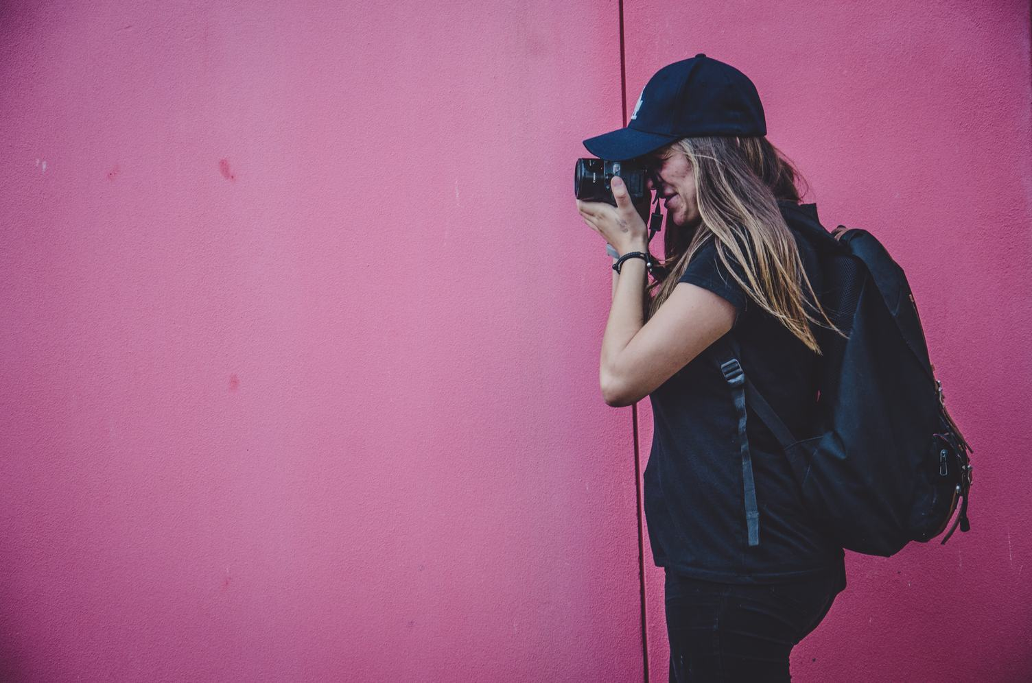 Female Photographer Shooting on a Pink Wall Background