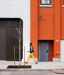 Man Walking Through a Orange Wall