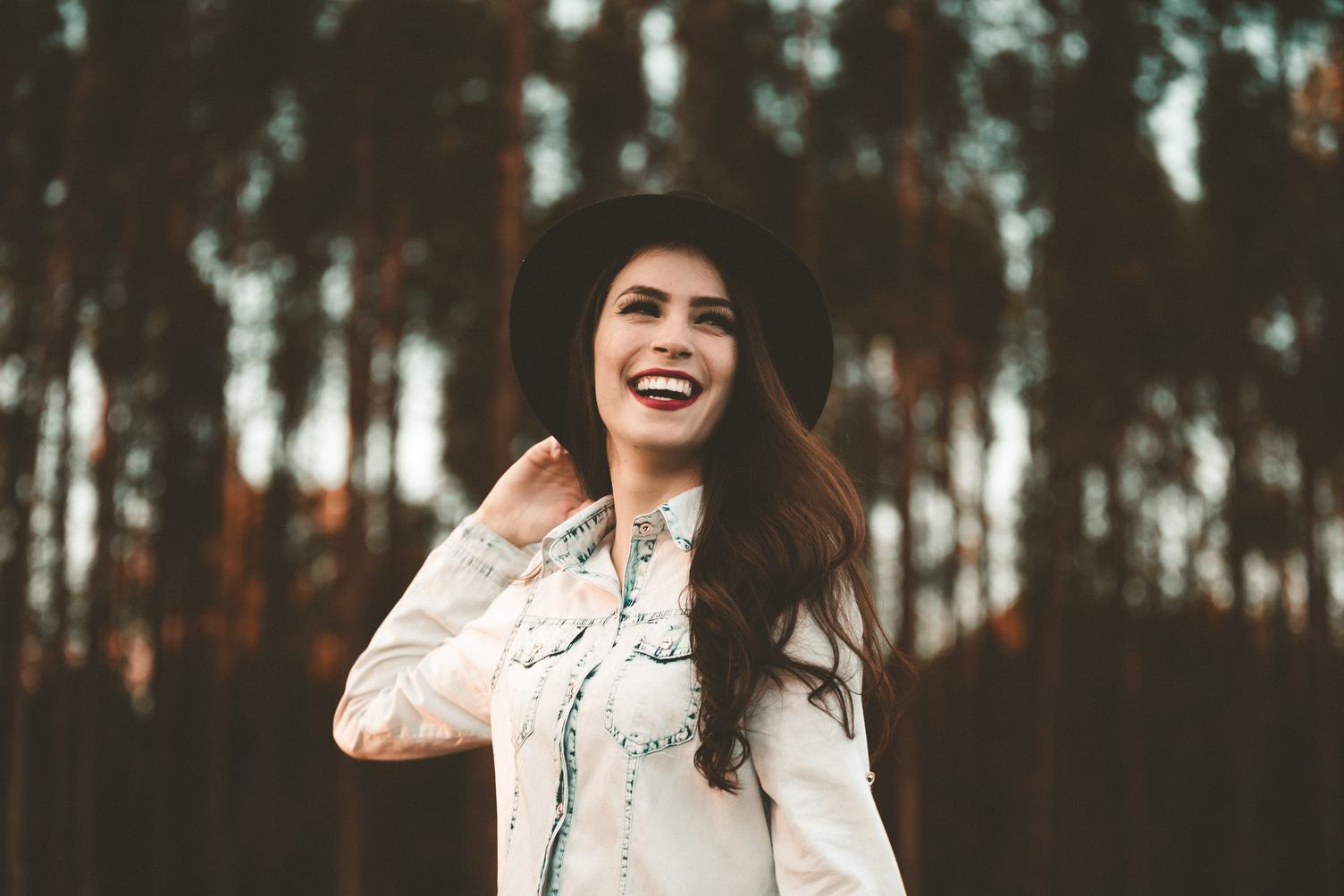 Stylish Young Woman Wearing Black hat Smiling against Blurred Trees