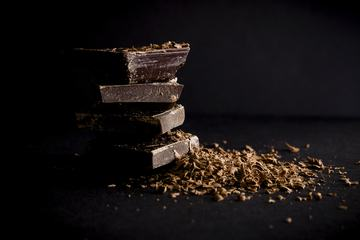 Dark Chocolate Stack and Chips on Black Background