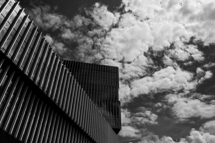 Modern Office Building with Facade of Glass against Sky with Clouds