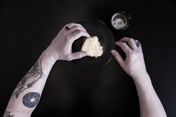 Close up of a Tattooed Man's Arms Eating Breakfast against Black Background