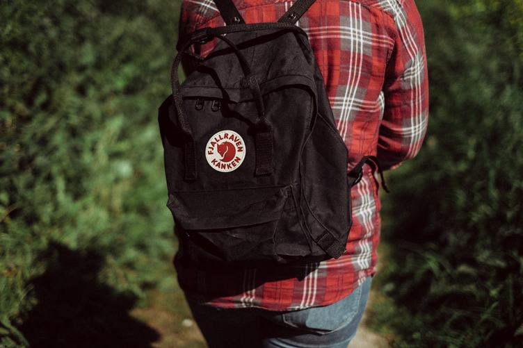 Person in Red Checkered Shirt with Black Backpack Walking