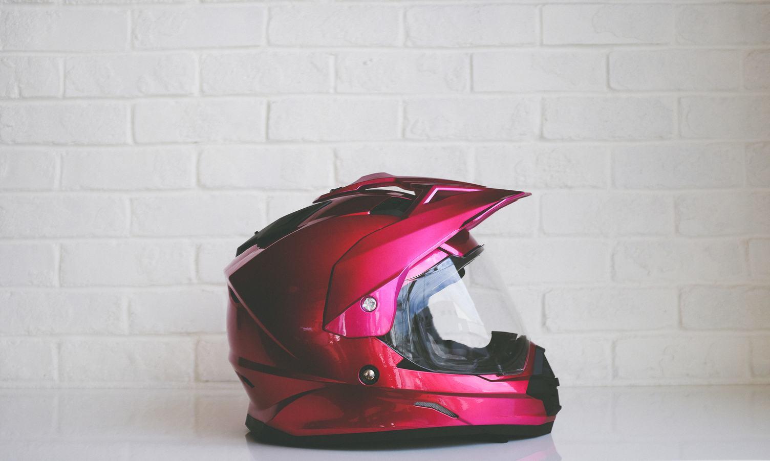 Red Metallic Motorcycle Helmet against White Brick Wall