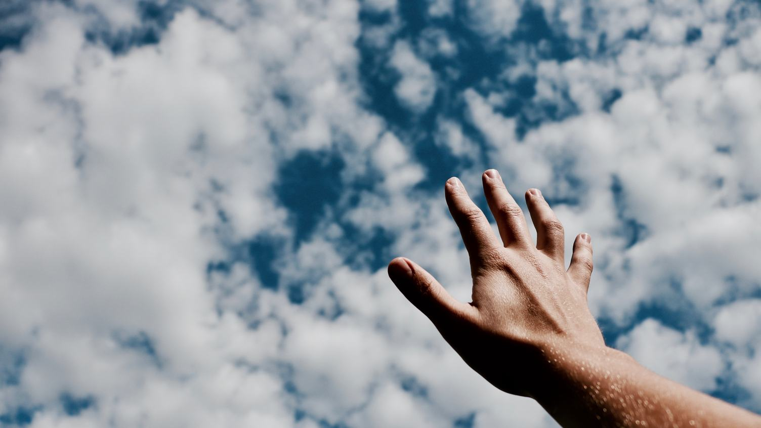 Human Hand against Blue Sky with Clouds