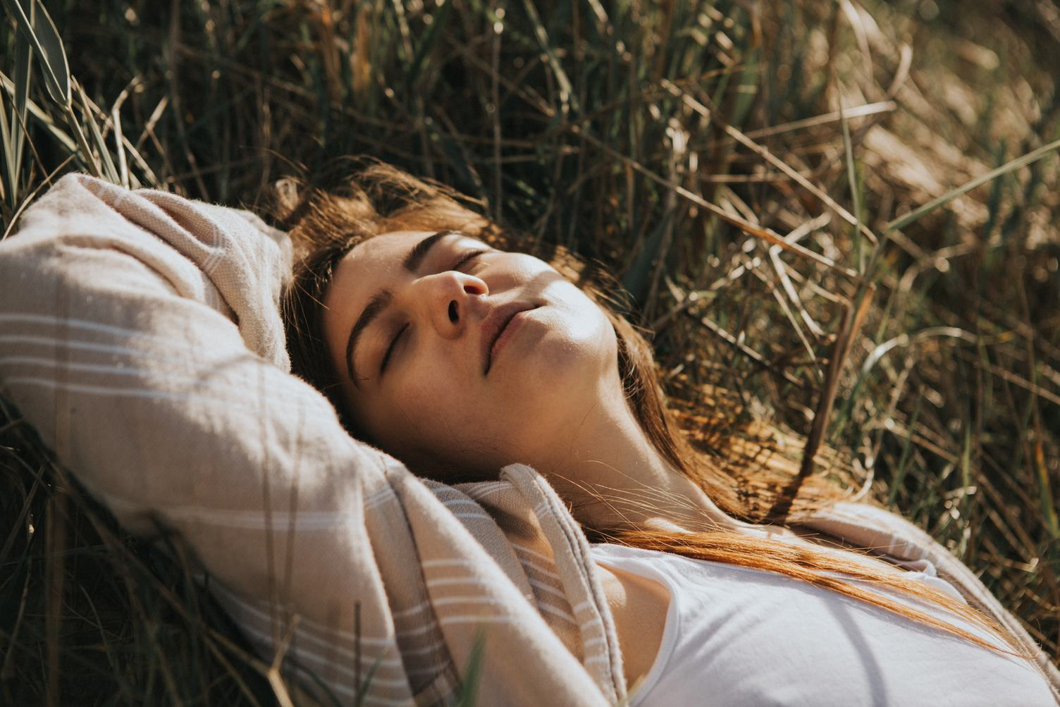 Young Woman Relaxing Lying on the Grass with Closed Eyes Enjoying Sunlight