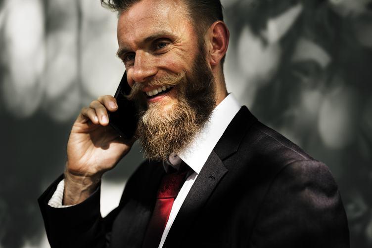 Happy Man Wearing Elegant Black Suit Talking on the Phone