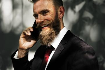 Happy Man Wearing Elegant Black Suit Talking on the Phone