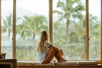 Young Blond Woman Sitting on a Window Looking Outside