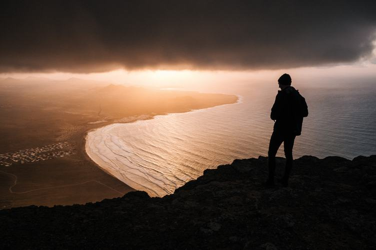 Man Silhouette High on Cliff at Sunset