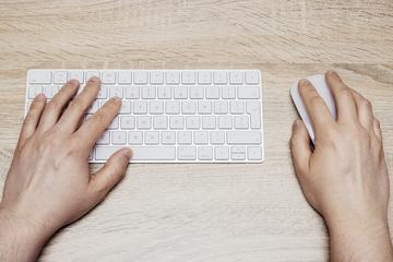 Man Typing on White  Keyboard