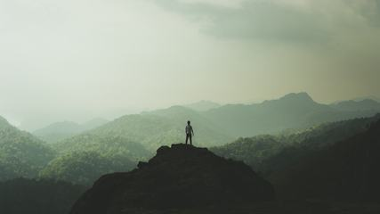 Man Standing on Top of a Mountain and Enjoying View