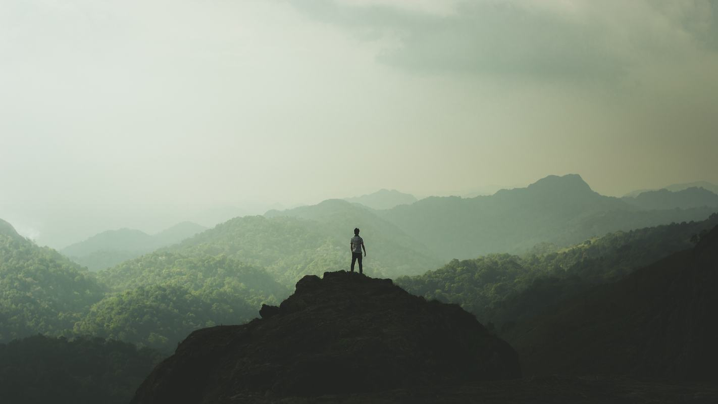 Free Photo Man Standing On Top Of A Mountain And Enjoying