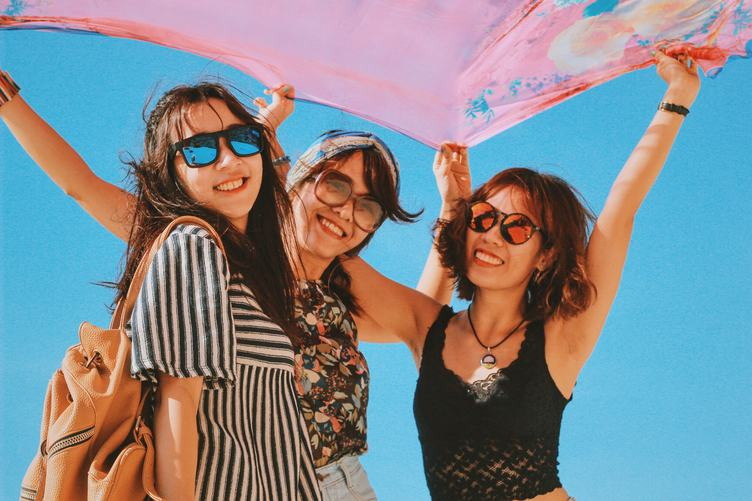 Three Girls Holding Pink Shawl against the Blue Sky