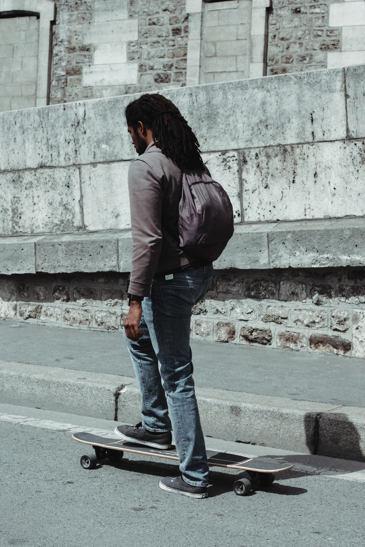 Young Black Man with Dreadlocks Getting on his Skateboard