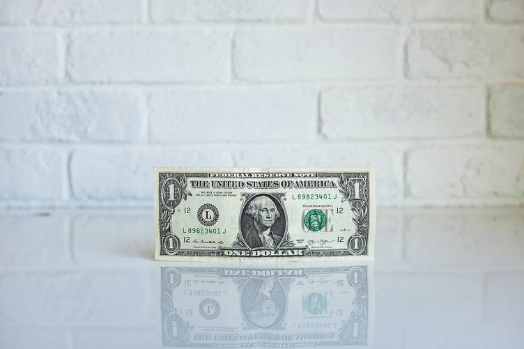 One Dollar Banknote against White Brick Wall