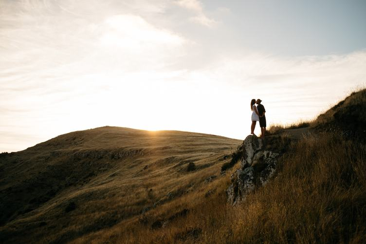 Young Couple Kissing on the Rock at Sunset
