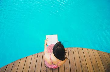 Top View of Woman Sitting on a Pier and Reading