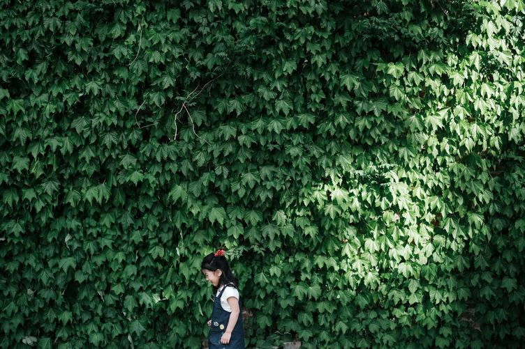 A Little Girl Standing and Laughing against Green Leaves Wall
