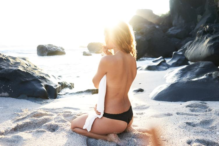 Beautiful Sensual Woman Sitting from the Back on Beach