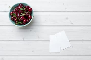 Empty Tag Cards and Cherries in Bowl on White Wooden Background