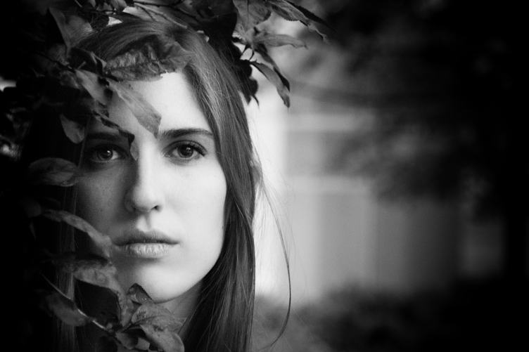 Black and White Portrait of a Beautiful Young Woman Hidden in the Leaves
