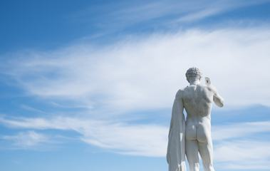 Ancient Statue of a Young Man from the Back against Blue Sky