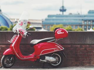 Red Vespa Scooter Parked by the Small Brick Wall