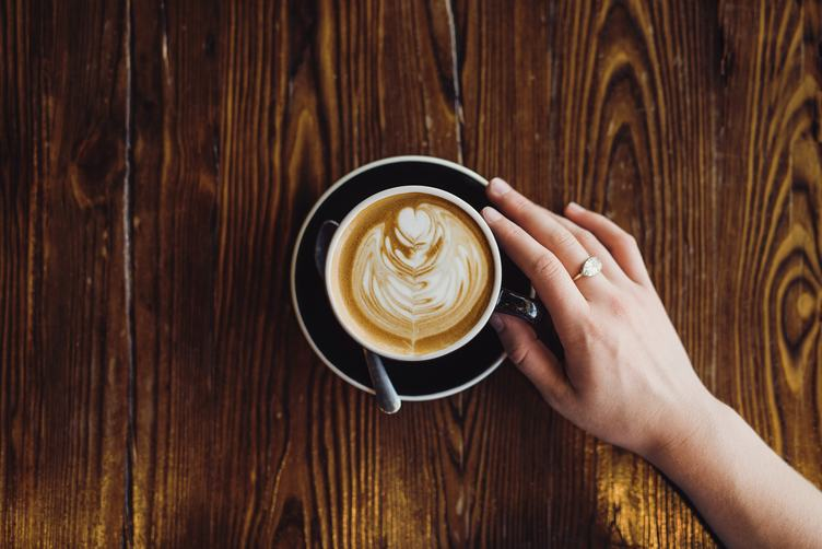 Feale Hand Holding Cup of Coffee
