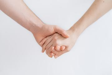 Man and Woman Holding Hands against White Background