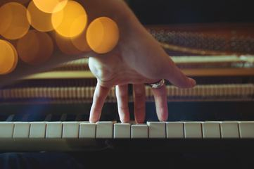 Close Up of Left Hand of a Young Woman Playing Piano