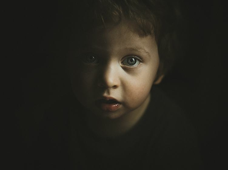 Face of Little Boy Emerging from Darkness