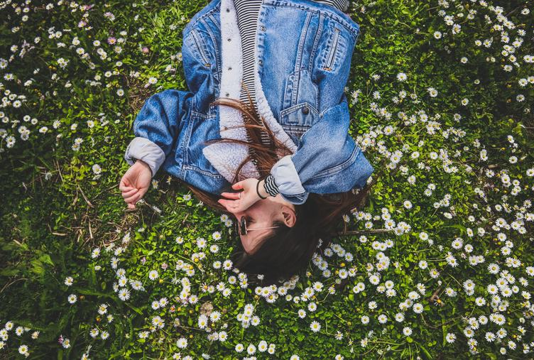 Young Brunette Enjoying Lying on the Grass full of Daisies