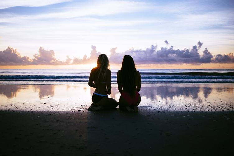 Two Young Woman Sitting on the Beach during Sunset
