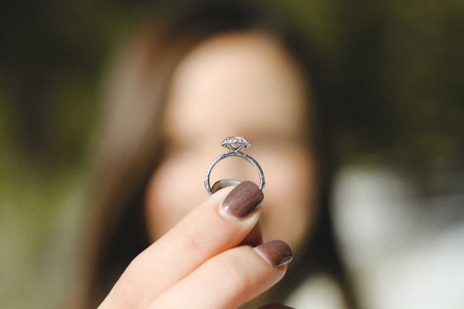 Woman Holding Engagement Ring in her Hand