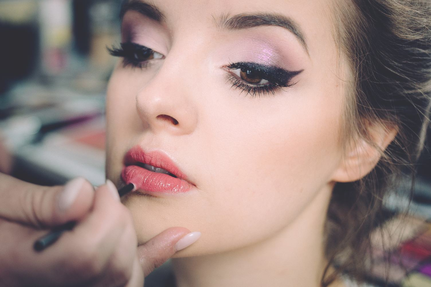 Makeup Artist Applies Lipstick Beautiful Woman Face. Perfect Makeup