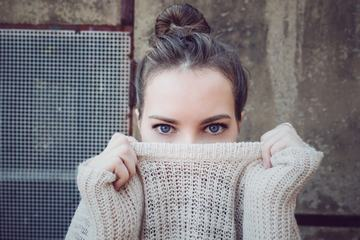 Young Woman Face Hidden behind Sweater