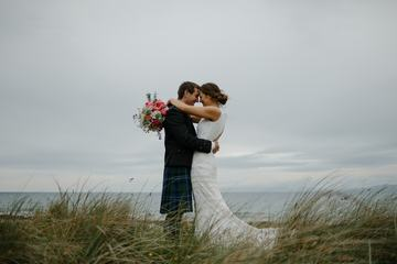 Happy and Lovely Wedding Couple Cuddling on the Beach