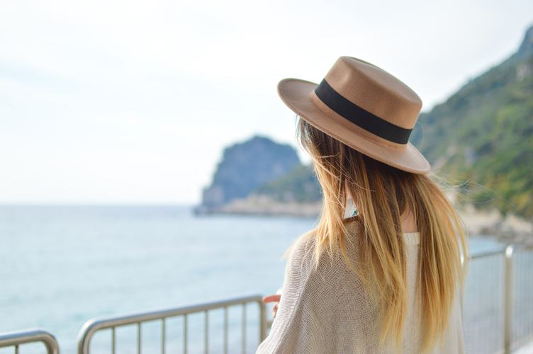 Back Beautiful Girl with Long Blond Hair against the Sea