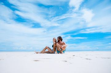 Couple Sitting on the Beach against Blue Sky