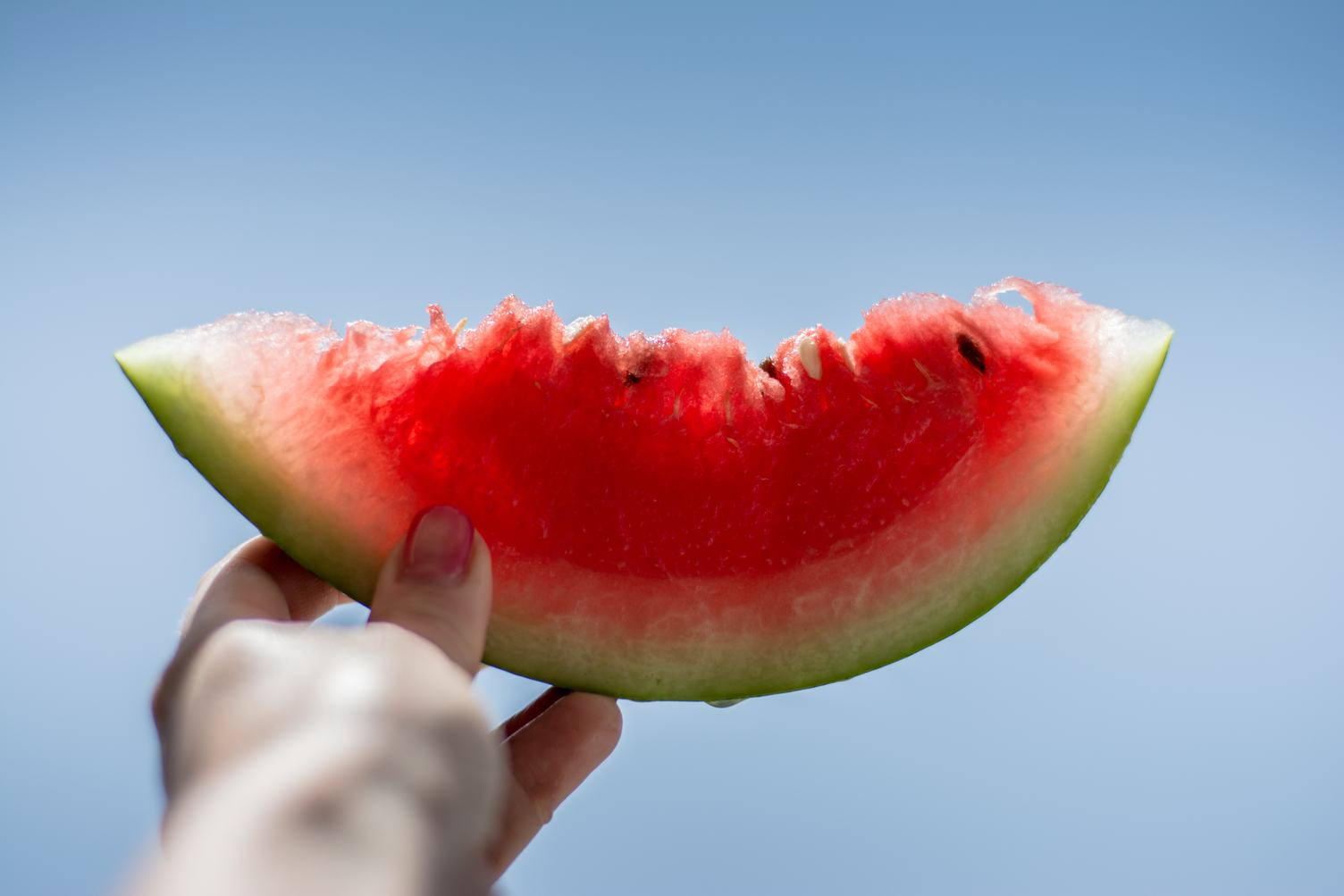 Woman Holding Juicy Slice of Watermelon in Her Hand