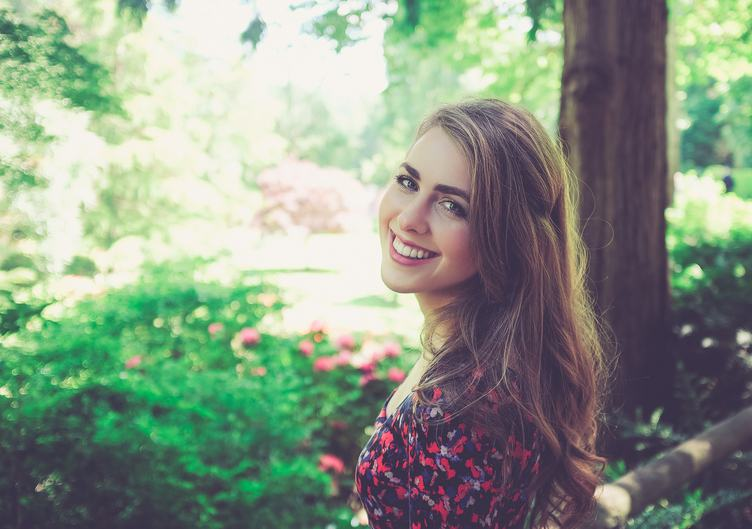 Portrait of Young Smiling Woman in the Garden
