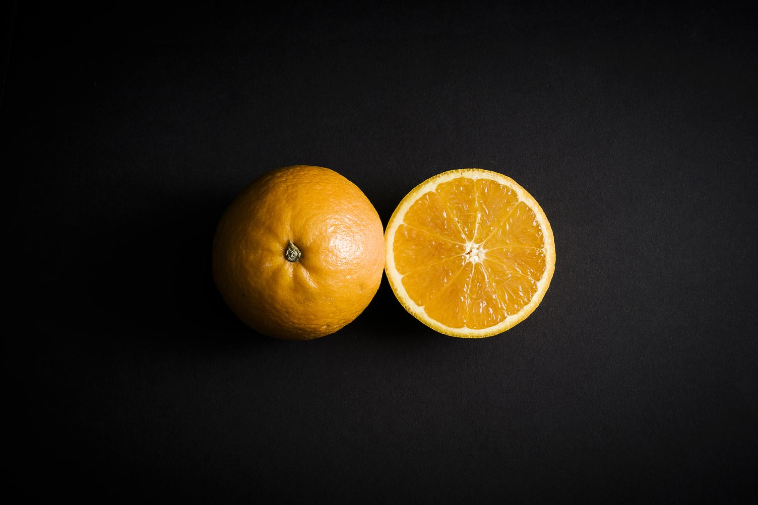 Orange Fruit Cut in Half on Black